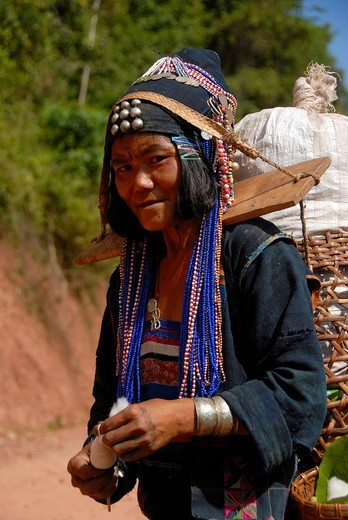 Poverty, portrait, woman of the Akha Djepia ethnic group, traditional colorful clothes, cap for a hat, spinning of cotton into yarn, carrying a load on a yoke on her shoulders, Ban Khay, Boun Tai district, province Phongsali, Laos, Southeast Asia, Asia : Stock Photo