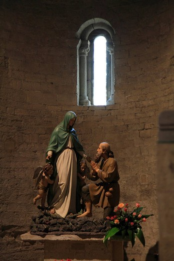 Statue of the Virgin Mary with a bearded man kneeling in front of her in front of Romanesque windows, Cathedral of Santa Maria Assunta, Romanesque, 11th to 12th Century, Ventimiglia, province of Imperia, Liguria region, Riviera dei Fiori, Mediterranean Se : Stock Photo