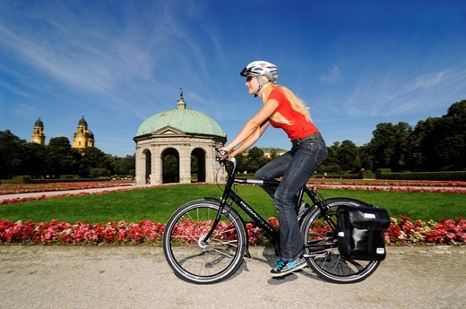 Young woman riding a bicycle, Hofgarten, Court Garden, Munich, Bavaria, Germany, Europe : Stock Photo