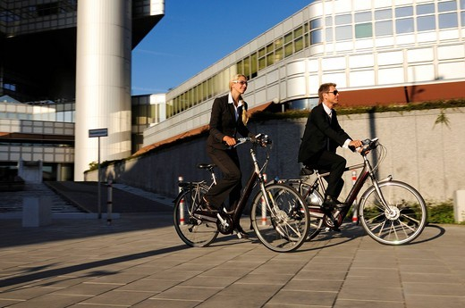 Business people riding on electric bicycles, pedelecs, Hypo_Hochhaus building, Munich, Bavaria, Germany, Europe : Stock Photo