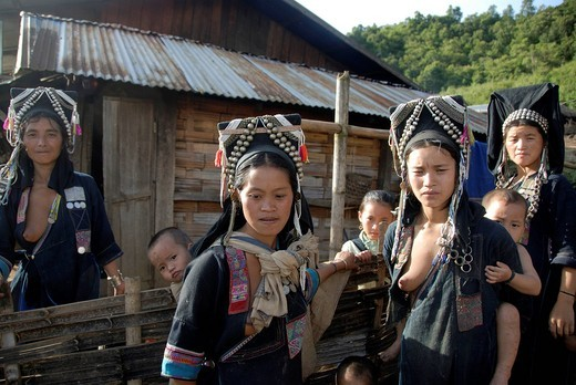 Stock Photo: 1848-440468 Poverty, Akha Nuqui women, with infants on their backs, dressed in indigo coloured traditional clothing and hats with silver jewellry in front of a hut, village of Ban Seochayneua, Phongsali province and district, Laos, Southeast Asia, Asia