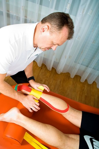 Stock Photo: 1848-442057 Physiotherapist giving a meditape treatment