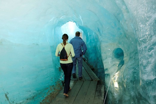 Hikers in a glacier cave, Rhone Glacier, Furka Pass, Uri, Switzerland, Europe : Stock Photo