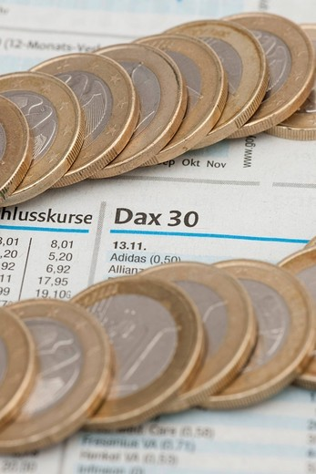 Stock Photo: 1848-442935 Coins on the stock exchange section of a newspaper, stock market