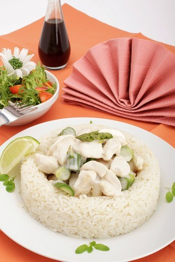 Chicken fricassee with mushrooms and green asparagus surrounded by a rice border, mixed salad : Stock Photo