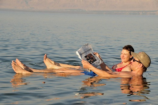 Tourists reading the newspaper in the Dead Sea near Suwaymah, Jordan, Middle East, Orient : Stock Photo