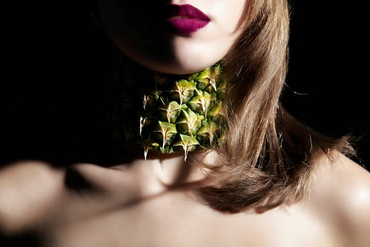 Portrait of a young woman wearing a necklace made of pineapple, jewellery : Stock Photo