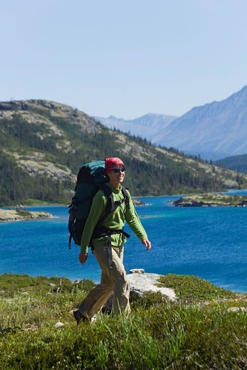 Stock Photo: 1848-446424 Young woman hiking, backpacking, hiker with backpack, historic Chilkoot Pass, Chilkoot Trail, Deep Lake behind, Yukon Territory, British Columbia, B. C., Canada