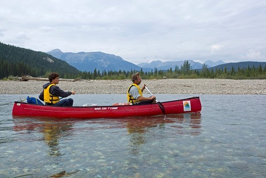 Two men in a canoe, canoeing upper Liard River, clear, shallow water, Pelly Mountains behind, Yukon Territory, Kanada : Stock Photo