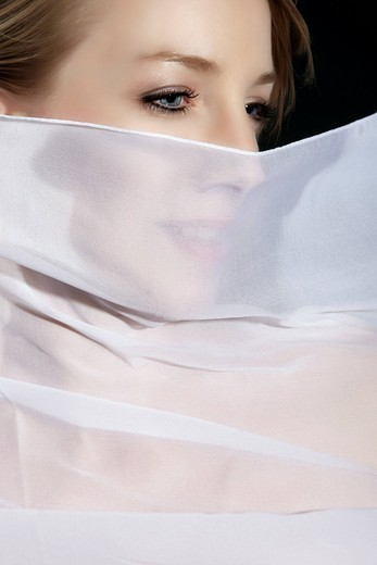 Portrait of a young woman with white silk fabric in front of her face : Stock Photo