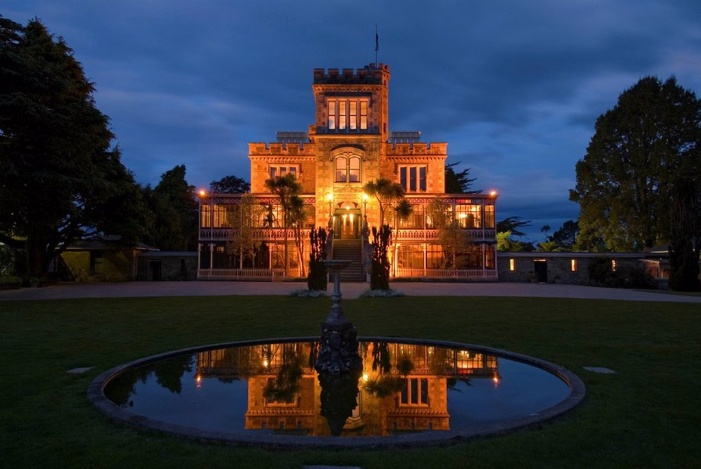 Larnach Castle on the Otago Peninsula and its reflexion in the pond of a fountain illuminated by floodlight, New Zealand : Stock Photo