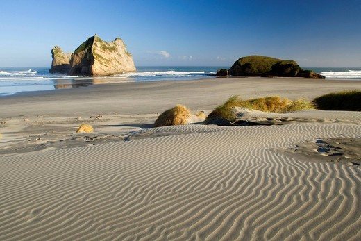 Rocky islands with caves and rock arches formed by water, at Wharariki Beach, Golden Bay, Nelson District, South Island, New Zealand : Stock Photo