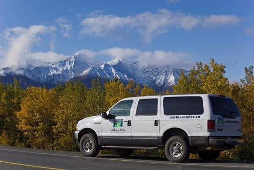 SUV driving along Alaska Highway, Indian Summer, trees in fall colours, St. Elias Mountains behind, Kluane National Park and Reserve, Yukon Territory, Canada : Stock Photo