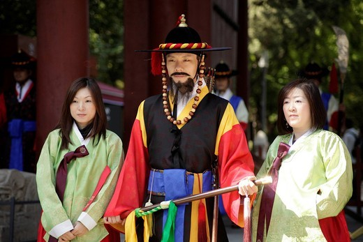 Young women posing with one of the guards in front of the Deoksugung royal palace, Palace of Longevity, in the Korean capital Seoul, South Korea, Asia : Stock Photo