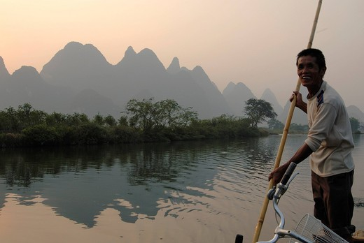 Bamboo raft with old Chinese man with a stake in the Yulong River in the rocky karst landscape near Yangshuo, Guilin, Guangxi, China, Asia : Stock Photo