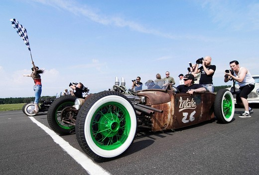 Starter girl starting a hot rod race, while photographers taking their pictures. Hot Rods, Kustoms, Cruisers & Art at the Bottrop Kustom Kulture 2007_Festival on the airfield in Bottrop_Kirchhellen, Germany, Europe : Stock Photo