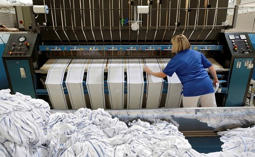 Stock Photo: 1848-45407 Janet Akgus working in the mangle hall at the handtowel rolls mangle machinery, Bardusch Uniform Rental & Laundry Services, Textil_Mietdienst Bardusch GmbH in Ettlingen, Baden_Wuerttemberg, Germany, Europe