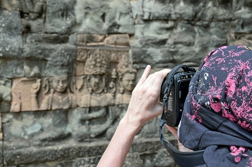 Woman taking pictures of weathered reliefs, Terrace of the Elephants, Angkor, Cambodia, Asia : Stock Photo