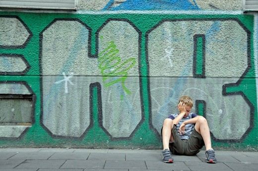 Stock Photo: 1848-455618 Frustrated nine_year_old boy in front of a graffiti wall, Germany, Europe
