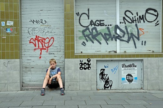 Lonely nine_year_old boy in front of a closed shop smeared with graffiti, Germany, Europe : Stock Photo