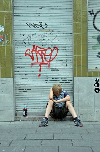 Stock Photo: 1848-455626 Lonely nine_year_old boy in front of a closed shop smeared with graffiti, Germany, Europe
