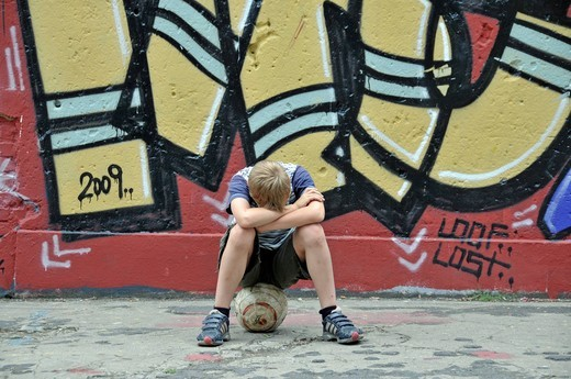 Disappointed and lonely boy with his football in front of a graffiti wall, kickabout area in Cologne, North Rhine_Westphalia, Germany, Europe : Stock Photo
