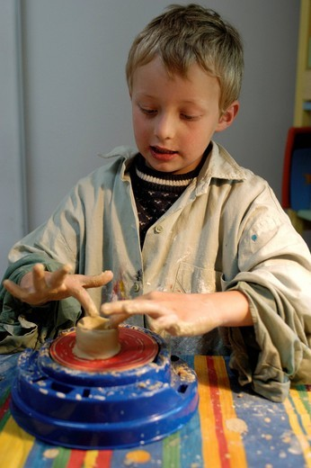 Little boy, 7, making pottery, turning a jar from clay on a potter´s wheel : Stock Photo