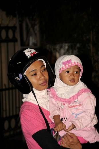Javanese woman with headscarf, Muslim, under helmet, with a baby, Yogjakart, Java, Indonesia, Southeast Asia : Stock Photo