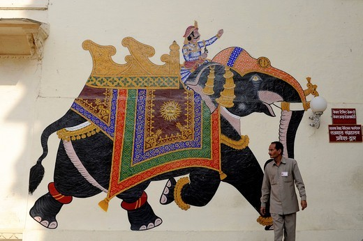 Indian in front of the mural of an elephant with a rider in the city palace, Udaipur, Rajasthan, North India, India, South Asia, Asia : Stock Photo