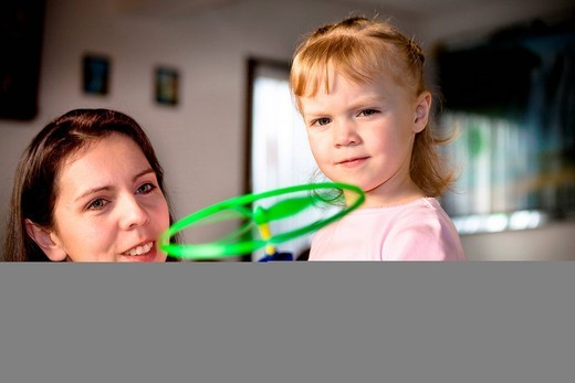 Mother showing her daughter how to use a new toy : Stock Photo