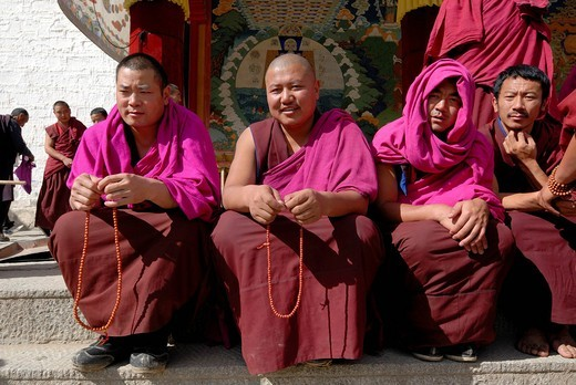 Stock Photo: 1848-459254 Tibetan monks wearing robes of the Gelug or Gelug_pa Order sitting in front of the Assembly Hall, Tibetan Dukhang, Labarang Monastery, Xiahe, Gansu, China, Asia