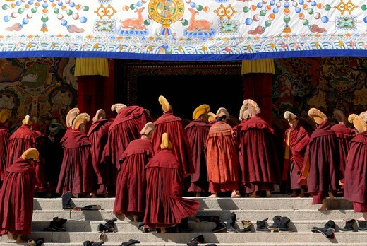 Stock Photo: 1848-459816 Tibetan monks wearing robes and yellow hats of the Gelug Order or Yellow Hat Sect on the stairs in front of the Assembly Hall, Tibetan Dukhang, the Labrang Monastery, Xiahe, Gansu, China, Asia