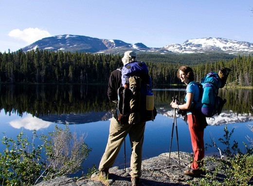 Hikers enjoying a view of glassy Dan Johnson Lake, Chilkoot Trail, British Columbia, Canada : Stock Photo