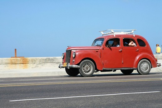 Car driving on Malecón Road alongside Estrecho de la Florida bay in Havana, Cuba, Caribbean, Americas : Stock Photo