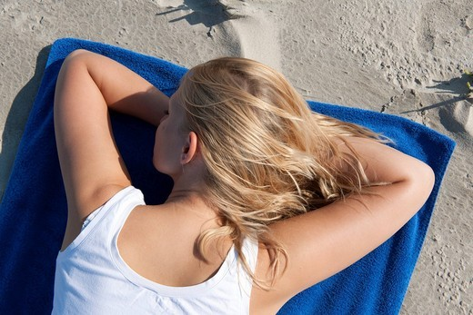 Young woman, 20_25 years, relaxing on a bright blue summer day on the beach of St Peter Ording, North Sea, North Friesland, Schleswig_Holstein, northern Germany, Germany, Europe : Stock Photo