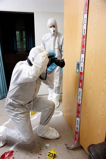 Photographic securing of forensic evidence, by officer of the C.I.D., the Criminal Investigation Department, gathering forensic evidence at the scene of a crime, after a capital offence, homicide, re_enacted scene : Stock Photo