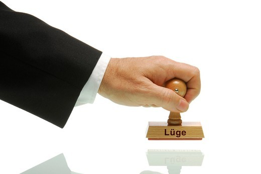 Manager hand holding a stamp labelled Luege, German for lies : Stock Photo