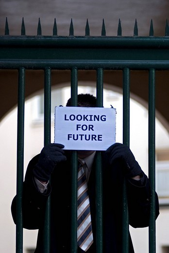 Man standing behind bars holding a sign with the message, Looking for future, symbolic image for the economic crisis : Stock Photo