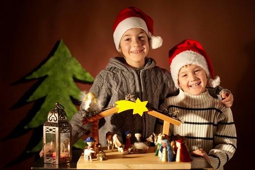 Two children and a nativity scene : Stock Photo