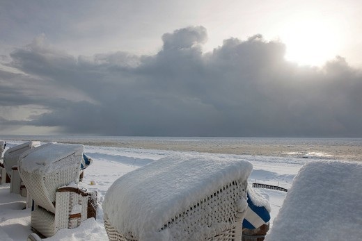 Snow_covered wicker beach chairs overlooking a snow and ice landscape on the south beach of Wyk of the North Sea island of Foehr, Nationalpark Schleswig_Holsteinisches Wattenmeer, Schleswig_Holstein Wadden Sea National Park, Unesco World Heritage Site, No : Stock Photo
