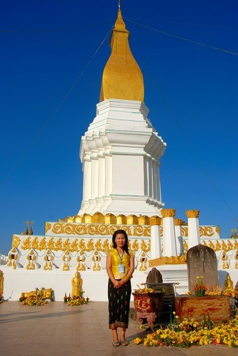 Stock Photo: 1848-471569 Laotian woman standing in front of a large stupa in white and gold, skirt, Sin, Pha That Si Kotabong, Tha Khek, Khammouan province, Laos, Southeast Asia, Asia