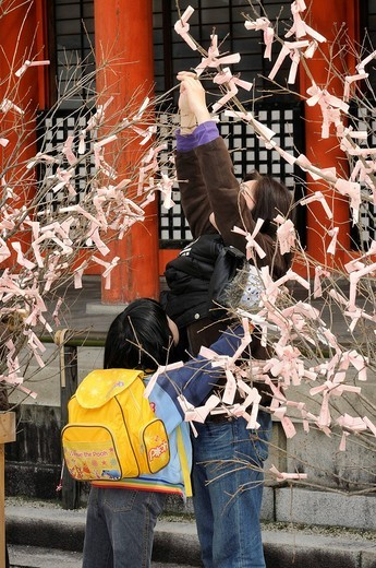 Stock Photo: 1848-47172 Japanese girl and her mother knot prayers and wishes to the shrubs in the Shinto Heian Shrine, Kyoto, Japan, Asia