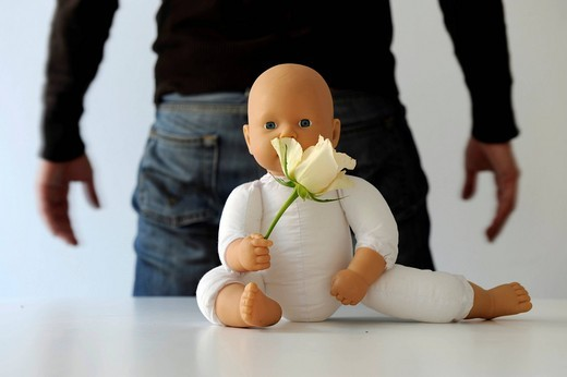 Stock Photo: 1848-472658 Man standing behind a baby doll, symbolic picture illustrating child abuse, child maltreatment, sexual abuse