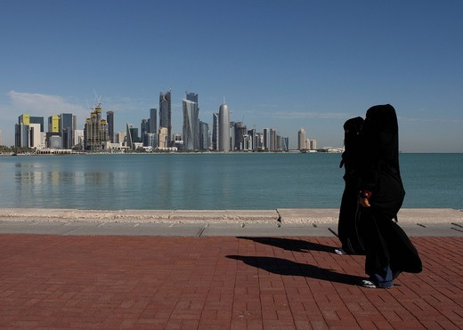 Stock Photo: 1848-473084 Arabian women wearing traditional black robes walking along the Corniche in front of the skyline, West Bay District, Doha, Qatar, Middle East