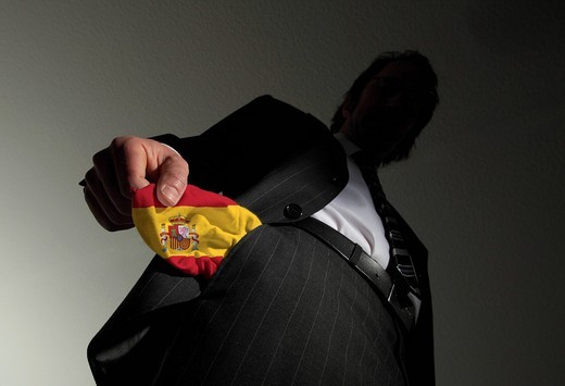 Man in a suit with empty pockets in the national colours of Spain, symbolic image for national bankruptcy of Spain : Stock Photo