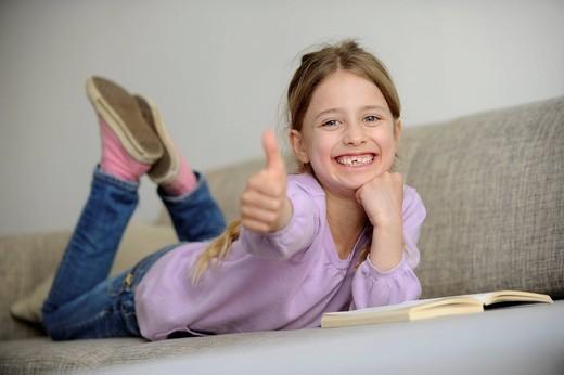 Stock Photo: 1848-476133 Girl, eight years, has fun reading