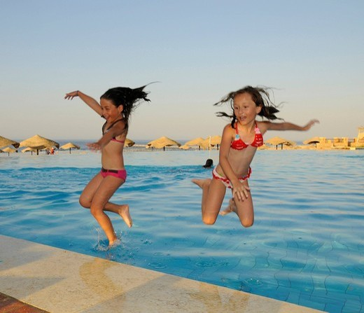 Two girls, eight years, jumping into a pool : Stock Photo