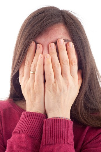 Woman in her mid forties, holding her hands in front of her face : Stock Photo