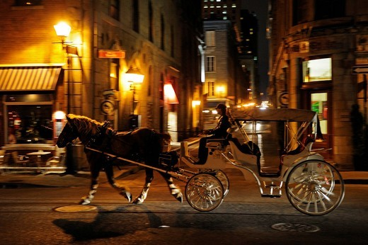 Stock Photo: 1848-477512 Horse_drawn carriage for tourists driving at night through the streets of the historic old town of Montreal, Quebec, Canada