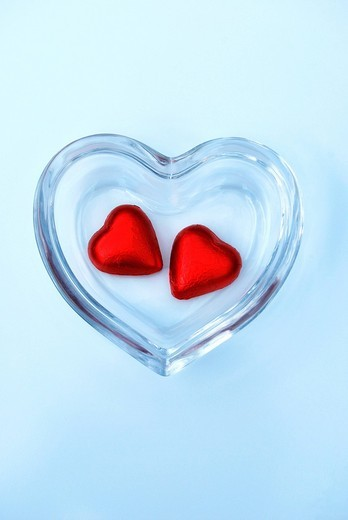 Stock Photo: 1848-478135 Two heart_shaped chocolates in a glass bowl, symbolic image for togetherness
